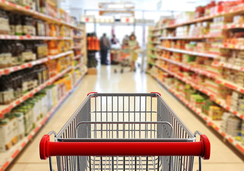 Supermarket shopping. Shopping cart, empty, with red handle on blur grocery aisle background. 3d illustration